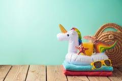 Fondo di vacanze estive con il galleggiante dello stagno dell'unicorno e del succo d'arancia sulla tavola di legno fotografie stock libere da diritti
