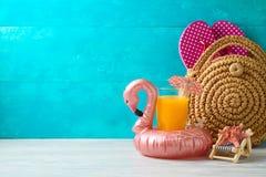Fondo di vacanze estive con succo d'arancia, la borsa di modo ed il galleggiante dello stagno del fenicottero sulla tavola di leg fotografia stock libera da diritti