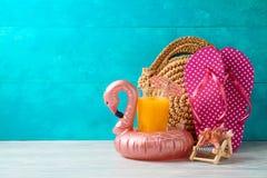 Fondo di vacanze estive con succo d'arancia, la borsa di modo ed il galleggiante dello stagno del fenicottero sulla tavola di leg fotografia stock