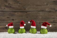 Fondo divertido de la Navidad con las bolas y los sombreros verdes de santa en el wo Foto de archivo libre de regalías