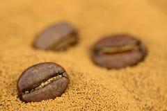 Fondo dorato del caffè istantaneo con i chicchi di caffè fotografia stock libera da diritti