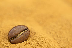 Fondo dorato del caffè istantaneo con il chicco di caffè fotografia stock