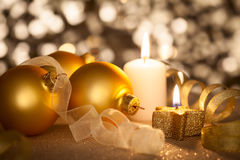 Fondo dorato di Natale con le candele, le bagattelle ed i nastri Fotografia Stock Libera da Diritti