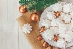 Fondo dulce de la Navidad con los merengues airosos, la rama del abeto, las bellotas de oro y las bolas en la placa Fotos de archivo