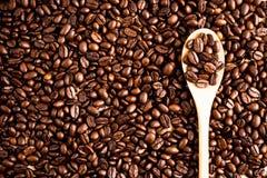 Fondo e struttura arrostiti del chicco di caffè con il cucchiaio di legno, co immagini stock libere da diritti