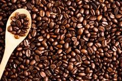Fondo e struttura arrostiti del chicco di caffè con il cucchiaio di legno, co immagine stock