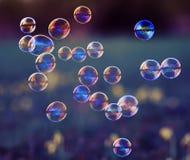 Fondo elegante con las burbujas de jabón brillantes que vuelan sobre un florido Fotos de archivo