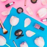 Fondo en colores pastel azul y rosado con las flores y los cosméticos femeninos Endecha plana Visión superior Foto de archivo
