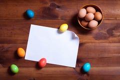 Fondo felice della carta di pasqua, uova e Libro Bianco in bianco sulla tavola di legno marrone immagine stock