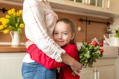 Fondo felice di compleanno o di festa della Mamma Ragazza adorabile che abbraccia la sua mamma dopo sorprendente lei con il mazzo immagini stock libere da diritti