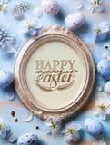 Fondo felice di Pasqua; Fiori dell'uovo di Pasqua e della molla sulla t blu immagini stock