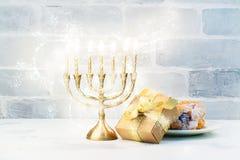 Fondo feliz de Jánuca con el menorah, las velas ardientes y donu Fotografía de archivo