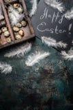 Fondo feliz de Pascua con las plumas, los huevos de codornices y la pizarra, visión superior Imagenes de archivo