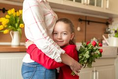 Fondo feliz del día o del cumpleaños de madre Chica joven adorable que abraza a su mamá después de asombrosamente ella con el ram imágenes de archivo libres de regalías