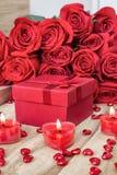 Fondo festivo al día de tarjeta del día de San Valentín Un ramo de rosas rojas, de una caja de regalo y de una vela en forma de c fotos de archivo