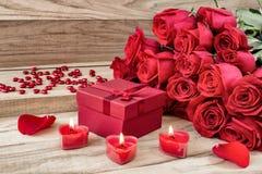 Fondo festivo al día de tarjeta del día de San Valentín Un ramo de rosas rojas, de una caja de regalo y de una vela en forma de c fotografía de archivo libre de regalías