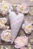 Fondo festivo con el corazón decorativo y el flowe rosado de las peonías Foto de archivo