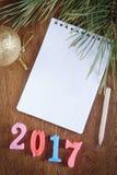 Fondo festivo con il blocco note in bianco circa il buon anno 2017 Fotografia Stock