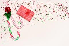 Fondo festivo con la caja de regalo, los bastones de caramelo y el confeti Fotografía de archivo