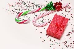 Fondo festivo con la caja de regalo, los bastones de caramelo y el confeti Fotos de archivo