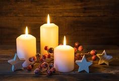 Fondo festivo de la Navidad con las velas ardientes, las estrellas y la decoración roja de las bayas Foto de archivo libre de regalías