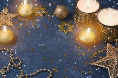 Fondo festivo de la Navidad con las velas y las decoraciones de oro sobre tablero oscuro Imágenes de archivo libres de regalías