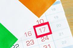 Fondo festivo del día del ` s de St Patrick Bandera irlandesa que cubre el calendario con la fecha enmarcada del 17 de marzo Fotografía de archivo
