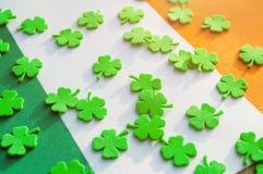 Fondo festivo del día del ` s de St Patrick Quatrefoils verdes claros sobre la bandera nacional irlandesa Imagen de archivo