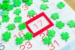 Fondo festivo di giorno del ` s di St Patrick I quatrefoils verdi che coprono il calendario di rosso hanno incorniciato il 17 mar Immagini Stock