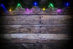 Fondo festivo di Natale o del nuovo anno di vecchi bordi di legno scuri, della ghirlanda d'ardore delle luci e delle palle colora immagini stock