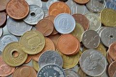 Fondo financiero que consiste en monedas de muchos países diferentes en la caja del metal imagenes de archivo