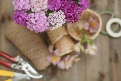 Fondo floristico degli strumenti Fiori rosa del garofano di Alstromeria su fondo di legno con gli strumenti floristici del giardi Fotografia Stock