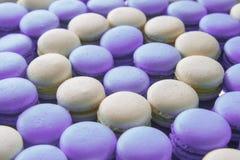 Fondo francés del desierto de Macaron muchos macarrones blancos y púrpuras imagen de archivo