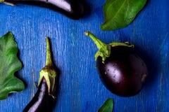 Fondo fresco della melanzana con la foglia Vista superiore Tavola rustica blu Immagini Stock