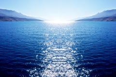 Fondo grande azul de la dimensión del extracto con el mar, cielo y con el sol blanco que entra en el mar y deja la reflexión en s fotos de archivo