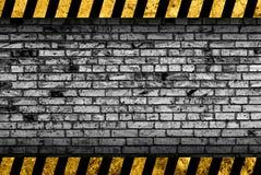 Fondo grigio del muro di mattoni di lerciume con le bande d'avvertimento illustrazione di stock