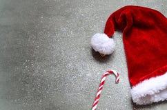 Fondo gris de la Navidad con el sombrero de Papá Noel Feliz Año Nuevo Foto de archivo libre de regalías