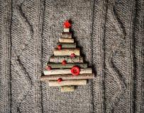 Fondo hecho punto caliente de la Navidad con las decoraciones del árbol del Año Nuevo hechas de palillos Tarjeta de Navidad del v Imagen de archivo libre de regalías