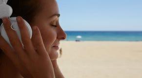 Fondo hermoso de la playa del mar de los auriculares del jugador de música de la mujer joven del retrato del primer que escucha L Imagenes de archivo