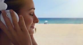 Fondo hermoso de la playa del mar de los auriculares del jugador de música de la mujer joven del retrato del primer que escucha L Foto de archivo