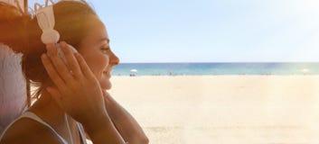 Fondo hermoso de la playa del mar de los auriculares del jugador de música de la mujer joven del retrato que escucha La muchacha  Fotos de archivo