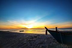 Fondo hermoso de la salida del sol de la puesta del sol en la playa con el barco de la silueta en el primero plano Imagen de archivo