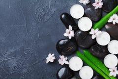 Fondo hermoso del balneario con el guijarro del masaje, las hojas verdes, las flores y las velas en la opinión de sobremesa de pi Foto de archivo