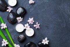 Fondo hermoso del balneario con el guijarro del masaje, las hojas verdes, las flores y las velas en la opinión de sobremesa de pi Imagen de archivo