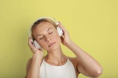 Fondo hermoso del color del amarillo del espacio en blanco del jugador de música de los auriculares de la mujer joven del retrato Fotografía de archivo libre de regalías