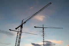 Fondo industrial abstracto con las siluetas de las grúas de construcción sobre el cielo de la puesta del sol imagenes de archivo