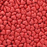 Fondo integrado por muchos pequeños corazones rojos Foto de archivo libre de regalías