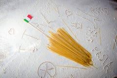 Fondo italiano de la comida, con espaguetis crudos y la bandera italiana Fotografía de archivo