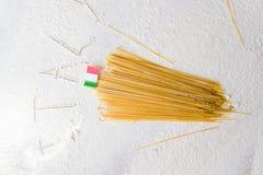 Fondo italiano de la comida, con espaguetis crudos y la bandera italiana Muestra de Italia escrita en la harina Fotos de archivo libres de regalías