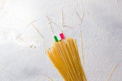 Fondo italiano de la comida, con espaguetis crudos y la bandera italiana Muestra de Italia escrita en la harina Imágenes de archivo libres de regalías